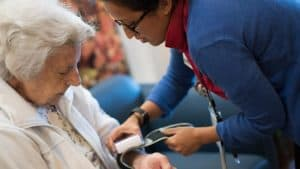 Nurse putting blood pressure monitor on senior woman