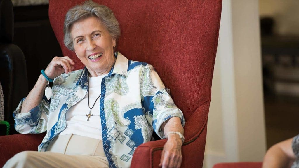 Senior woman sitting in red high-back chair smiling