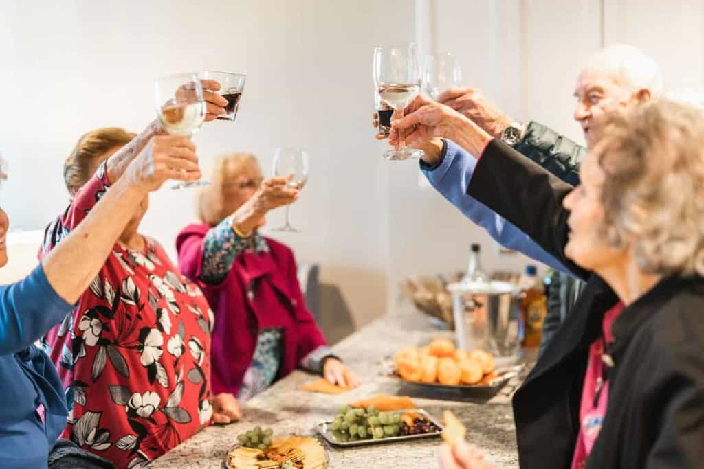 Seniors at gathering toasting drinks