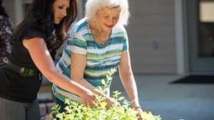 Staff member assisting senior woman with gardening